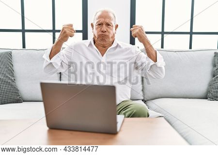 Senior man using laptop at home sitting on the sofa showing arms muscles smiling proud. fitness concept.