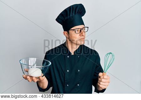 Handsome young man holding bread dough and blender smiling looking to the side and staring away thinking.
