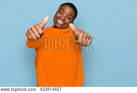 Young african american woman wearing casual clothes approving doing positive gesture with hand, thumbs up smiling and happy for success. winner gesture.