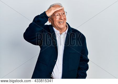 Senior man with grey hair wearing casual style and glasses very happy and smiling looking far away with hand over head. searching concept.