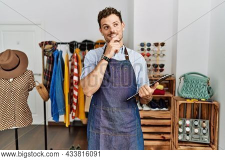 Handsome young man working as manager at retail boutique with hand on chin thinking about question, pensive expression. smiling and thoughtful face. doubt concept.