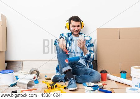 Happy Boy In Protective Headphones Sitting On Floor. Home Remodeling After Moving. Construction Tool