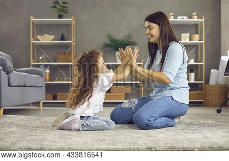 Young Woman And Her Daughter Enjoy Spending Time At Home Playing A Game Of Clapping.