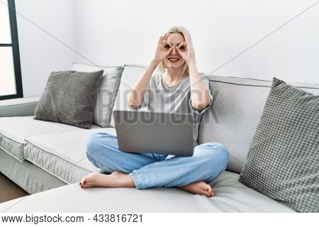 Young caucasian woman using laptop at home sitting on the sofa doing ok gesture like binoculars sticking tongue out, eyes looking through fingers. crazy expression.