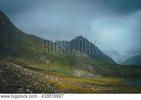 Dramatic Rainy Alpine Landscape With Low Rainbow In Green Valley And Dark Sharp Pinnacle In Low Clou
