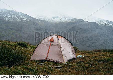 Scenic Alpine Landscape With Tent On Green Hill Among Rocks. Beautiful Snow-capped Mountains In Low