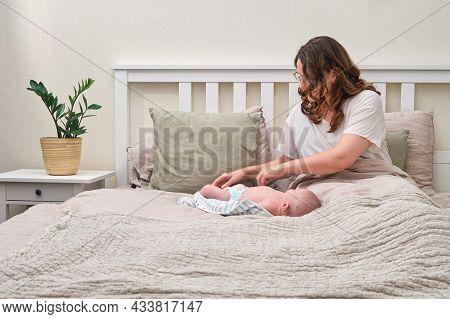 The Mother Changes The Child Clothes In The Bedroom. A Lonely Woman With A Newborn Baby Is Lying Alo