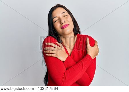 Young latin woman wearing casual clothes hugging oneself happy and positive, smiling confident. self love and self care