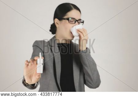 Allergy In A Young Woman In A Gray Jacket And Glasses. Allergy Nasal Spray In Hand. Selective Focus.