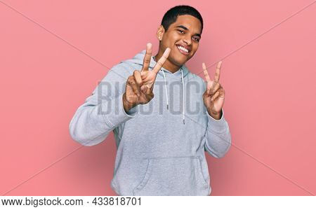 Young handsome hispanic man wearing casual sweatshirt smiling looking to the camera showing fingers doing victory sign. number two.