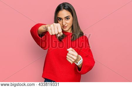 Beautiful brunette woman wearing casual winter sweater punching fist to fight, aggressive and angry attack, threat and violence