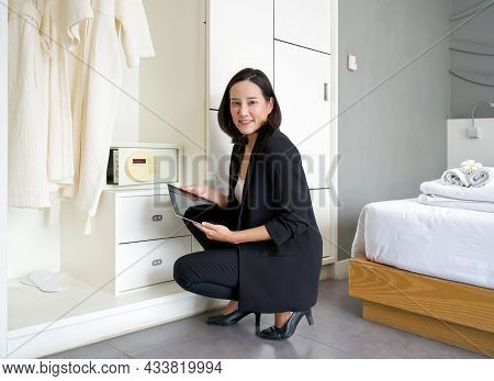 Asian Businesswoman In Black Suit Sitting With Tablet Computer In Her Hand. The Hotel Manager Verify