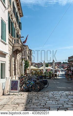 Tourists Walk In The Central Square Past A Large Bicycle Parking Lot In Rovinj, Croatia, August 30,