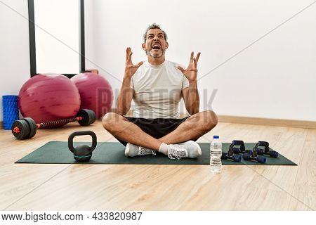 Middle age hispanic man sitting on training mat at the gym crazy and mad shouting and yelling with aggressive expression and arms raised. frustration concept.