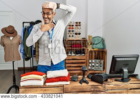 Middle age hispanic man working as manager at retail boutique smiling cheerful playing peek a boo with hands showing face. surprised and exited
