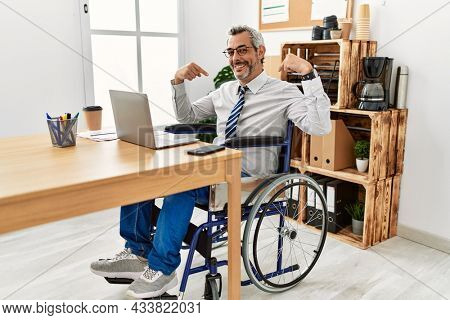 Middle age hispanic man working at the office sitting on wheelchair looking confident with smile on face, pointing oneself with fingers proud and happy.