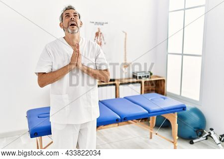 Middle age hispanic therapist man working at pain recovery clinic begging and praying with hands together with hope expression on face very emotional and worried. begging.