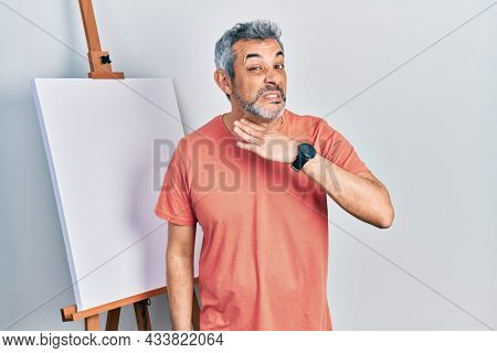 Handsome middle age man with grey hair standing by painter easel stand cutting throat with hand as knife, threaten aggression with furious violence