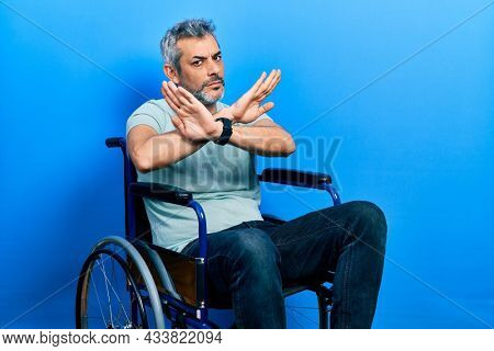 Handsome middle age man with grey hair sitting on wheelchair rejection expression crossing arms doing negative sign, angry face