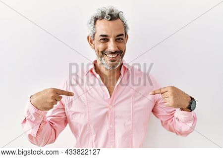 Middle age hispanic man standing over isolated background looking confident with smile on face, pointing oneself with fingers proud and happy.