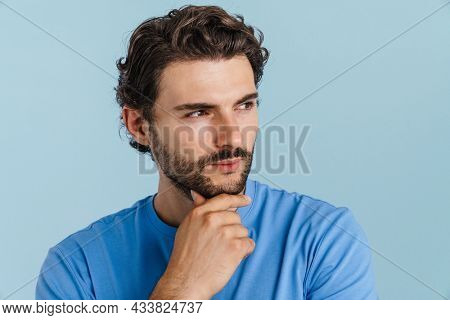 Young brunette man with bristle posing and looking aside isolated over blue background