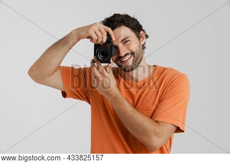Young brunette man with bristle smiling while taking photo isolated over white background