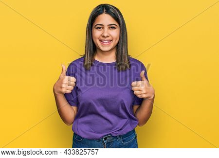Young hispanic girl wearing casual purple t shirt success sign doing positive gesture with hand, thumbs up smiling and happy. cheerful expression and winner gesture.