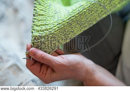 The Faceless Old Woman Knits. Close-up Of Female Hands With Straight And Knitting Needles.