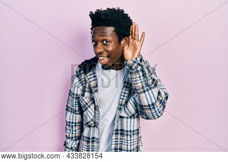 Young african american man wearing casual clothes smiling with hand over ear listening and hearing to rumor or gossip. deafness concept.