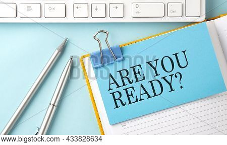 Are You Ready Text On Sticker On Blue Background With Pen And Keyboard