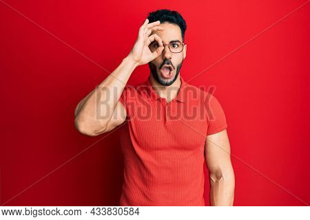Young hispanic man wearing casual clothes and glasses doing ok gesture shocked with surprised face, eye looking through fingers. unbelieving expression.