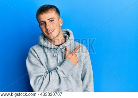 Young caucasian man wearing casual sweatshirt smiling cheerful pointing with hand and finger up to the side