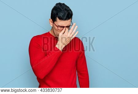 Handsome hispanic man wearing casual clothes and glasses tired rubbing nose and eyes feeling fatigue and headache. stress and frustration concept.