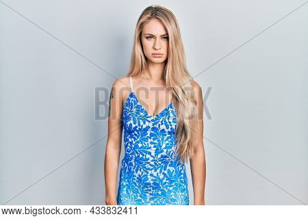 Young beautiful caucasian woman wearing summer dress skeptic and nervous, frowning upset because of problem. negative person.