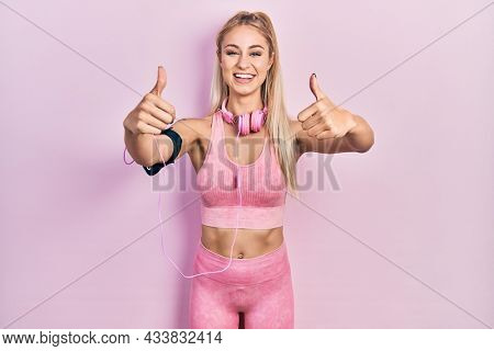Young beautiful caucasian woman wearing gym clothes and using headphones approving doing positive gesture with hand, thumbs up smiling and happy for success. winner gesture.