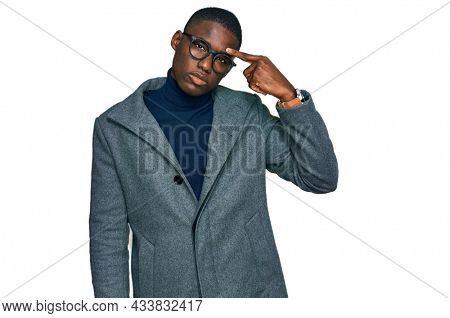 Young african american man wearing business clothes and glasses pointing unhappy to pimple on forehead, ugly infection of blackhead. acne and skin problem