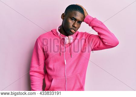 Young african american man wearing gym clothes and using headphones confuse and wonder about question. uncertain with doubt, thinking with hand on head. pensive concept.