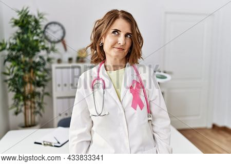 Middle age doctor woman wearing pink cancer ribbon on uniform smiling looking to the side and staring away thinking.