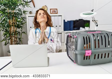 Middle age veterinarian woman working at pet clinic begging and praying with hands together with hope expression on face very emotional and worried. begging.