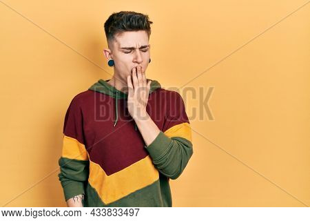 Young caucasian boy with ears dilation wearing casual sweatshirt bored yawning tired covering mouth with hand. restless and sleepiness.