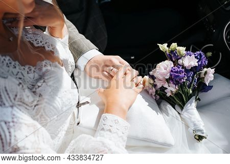 Wedding, Marriage Concept. Close-up Of Newlyweds Hand With Wedding Gold Rings On Top Of Each Other,