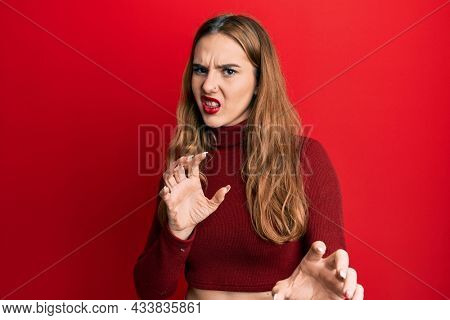 Young blonde woman wearing turtleneck sweater disgusted expression, displeased and fearful doing disgust face because aversion reaction. with hands raised