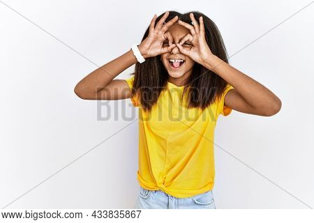 Young african american girl standing over white isolated background doing ok gesture like binoculars sticking tongue out, eyes looking through fingers. crazy expression.