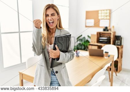 Blonde business woman at the office angry and mad raising fist frustrated and furious while shouting with anger. rage and aggressive concept.