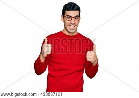 Handsome hispanic man wearing casual clothes and glasses success sign doing positive gesture with hand, thumbs up smiling and happy. cheerful expression and winner gesture.