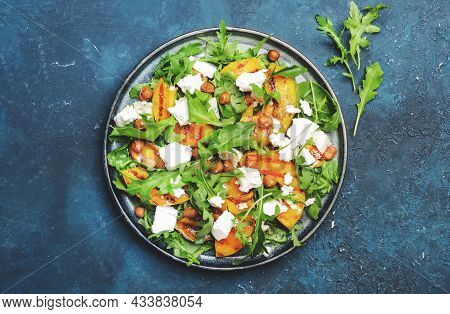 Grilled Peach Salad With Feta Cheese, Hazelnuts And Arugula On Blue Background, Top View, Copy Space