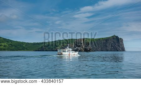 A White Boat Is Sailing On A Blue Ocean. A Trail Of Waves Astern. Picturesque Rocks On The Shore. Cl