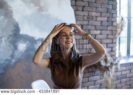 Portrait Of A Beautiful Young Business Woman With Brown Hair In A Brown Dress. Happy Smiling Girl Wi
