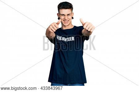 Young caucasian boy with ears dilation wearing volunteer t shirt approving doing positive gesture with hand, thumbs up smiling and happy for success. winner gesture.