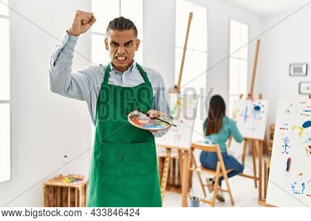 Young latin man standing at art studio annoyed and frustrated shouting with anger, yelling crazy with anger and hand raised